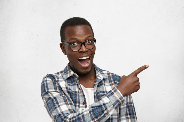 Animado e fascinado jovem estudante de pele escura em elegantes óculos e camisa quadriculada, indicando algo surpreendente