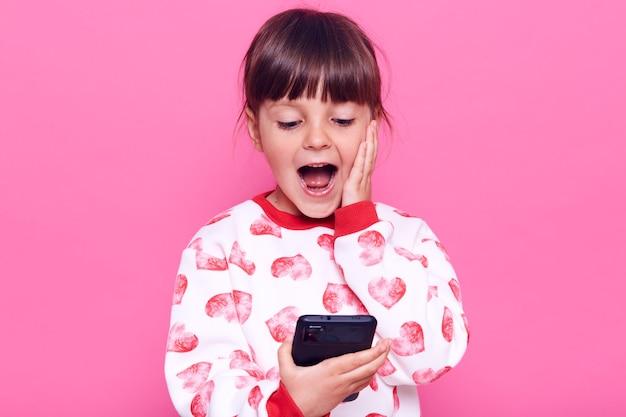 Animado e surpreso criança do sexo feminino no suéter estilo casual, segurando o telefone inteligente nas mãos e mantendo a boca aberta, tocando sua bochecha com a palma da mão, olha para o telefone, posando isolado sobre a parede rosa.
