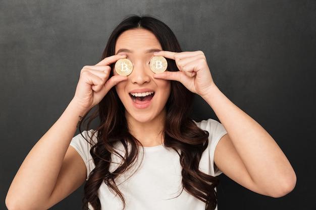 Animado emocional jovem asiática segurando dois bitcoins dourados, cobrindo os olhos.