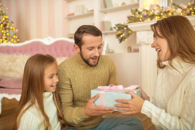 Animado. família jovem sentada no chão trocando presentes de natal