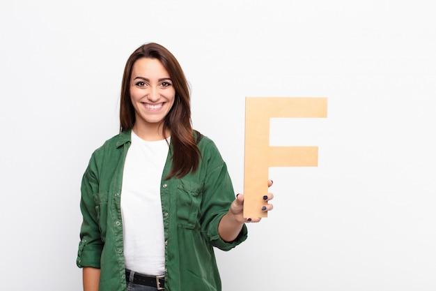 Animado, feliz, alegre, segurando a letra f do alfabeto para formar uma palavra ou frase.