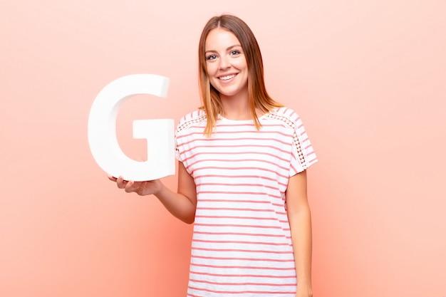 Animado, feliz, alegre, segurando a letra g do alfabeto para formar uma palavra ou frase.