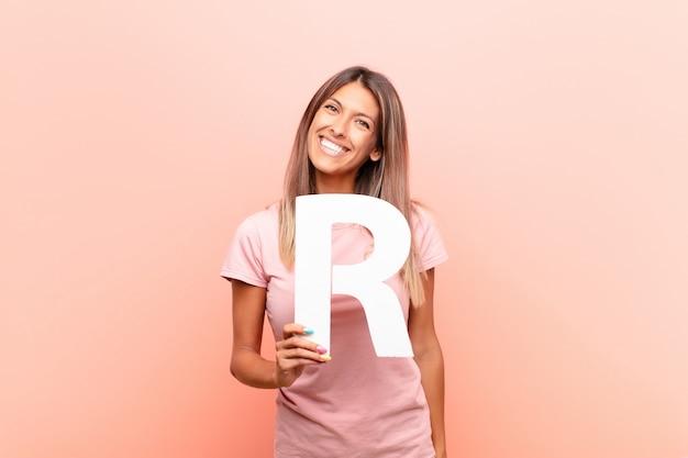 Animado, feliz, alegre, segurando a letra r do alfabeto para formar uma palavra ou frase.