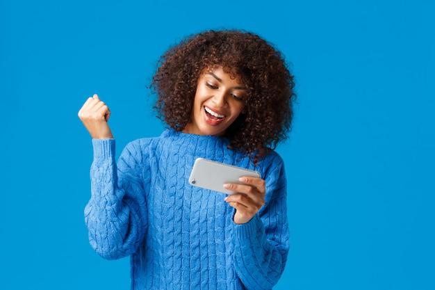 Animado feliz mulher afro-americana hipster na camisola de inverno, torcendo levantar punho alegremente triunfando