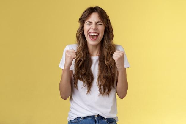 Animado, feliz, triunfando, alegre, menina, branca, olhos, punho, bomba, celebrando, felicidade, gesto, gritando, sim, sucesso, alcançar, objetivo, realização, dançar, vitória, vencer, sentir, aliviado, fundo amarelo