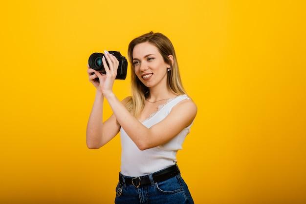 Animado fotógrafo feminino trabalhando em estúdio. retrato de uma menina loira deslumbrante com câmara fotográfica.