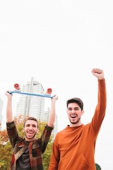Animado gritando modernos amigos do sexo masculino com cruzador