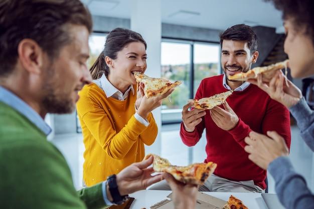 Animado grupo multicultural de empresários em pé na sala de reuniões comendo pizza no almoço.