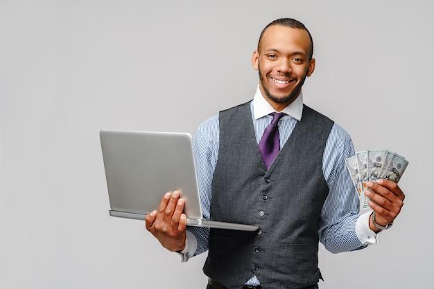 Animado jovem afro-americano segurando dinheiro e laptop sobre uma parede cinza claro