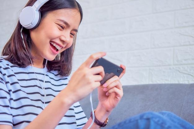 Animado jovem asiática sentada no sofá usar fone de ouvido branco na cabeça e jogando jogos no smartphone na sala de estar em casa.