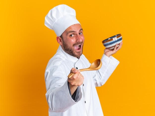 Animado jovem cozinheiro masculino caucasiano com uniforme de chef e boné olhando para a câmera, segurando a tigela, esticando a colher em direção à câmera, isolada na parede laranja