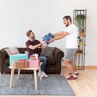 Animado jovem dando embrulhado caixa de presente para seu amigo em casa
