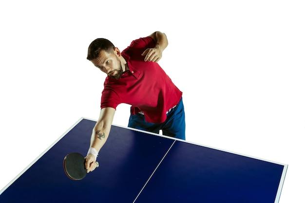 Animado. jovem joga tênis de mesa na parede branca. a modelo joga pingue-pongue. conceito de atividade de lazer, esporte, emoções humanas no jogo, estilo de vida saudável, movimento, ação, movimento.