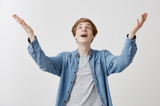 Animado jovem loiro em roupas jeans feliz que amigos vieram na festa, levanta as mãos com prazer, feliz em receber parabéns e presentes, comemora evento especial em sua vida
