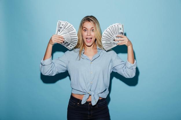 Animado jovem mulher bonita loira segurando o dinheiro nas mãos.