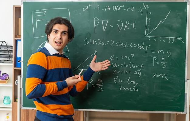 Animado jovem professor de geometria em pé em vista de perfil na frente do quadro-negro na sala de aula segurando o giz apontando para o quadro-negro