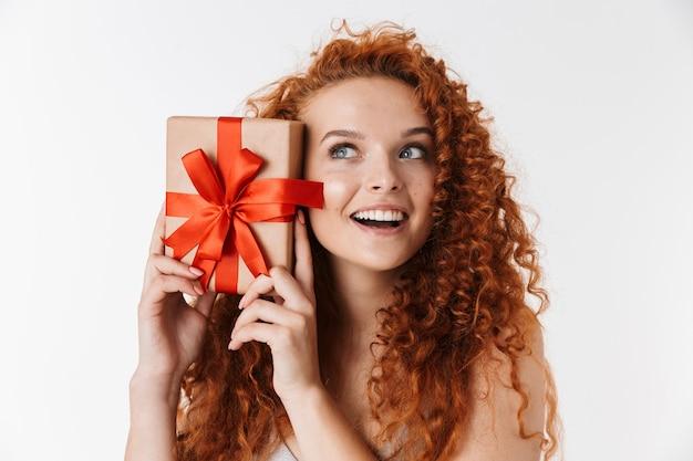 Animado jovem ruiva encaracolado segurando um presente de caixa surpresa.