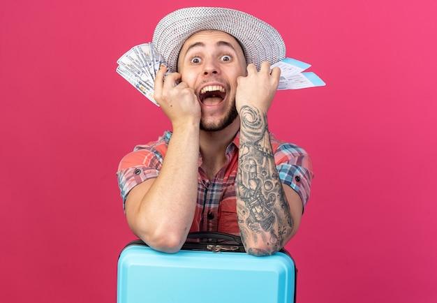 Animado jovem viajante com chapéu de palha de praia segurando passagens aéreas e dinheiro em pé atrás de uma mala, isolado na parede rosa com espaço de cópia