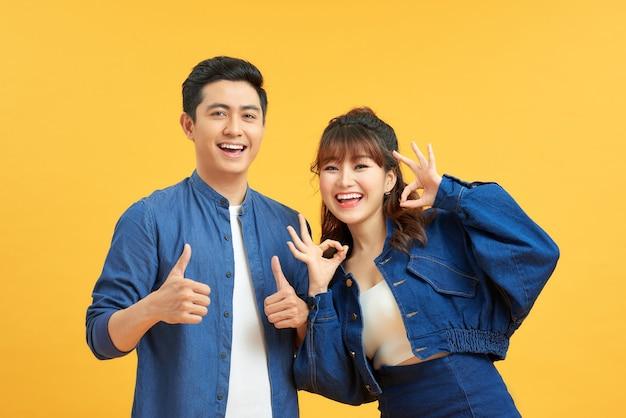 Animado lindo casal asiático mostra gesto de polegar para cima concorda em fazer algo e colaborar contra a parede laranja, fez um ótimo trabalho, mostra aprovação, como ideia. tudo ficará bem.