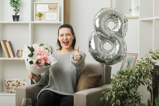 Animado mostrando o polegar para cima linda garota no dia da mulher feliz segurando buquê sentado na poltrona na sala de estar