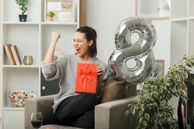 Animado, mostrando sim o gesto de menina bonita no dia da mulher feliz segurando um presente sentado na poltrona na sala de estar