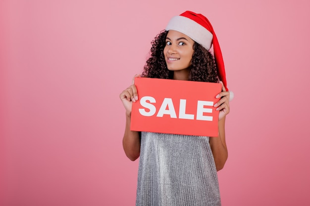 Animado mulher negra segurando copyspace sinal de venda vermelho e usando chapéu de papai noel isolado sobre rosa