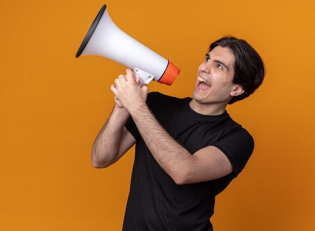 Animado olhando para o lado jovem bonito vestindo camiseta preta falando no alto-falante isolado na parede laranja