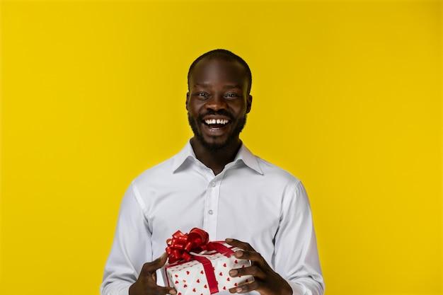 Animado sorridente barbudo jovem afro-americano está segurando um presente em duas mãos e olha na frente dele