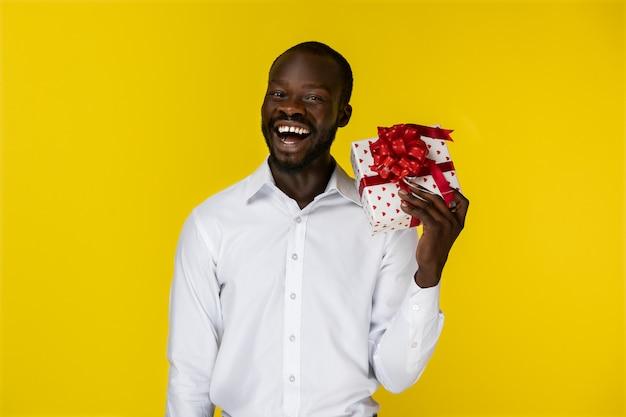 Animado sorridente barbudo jovem afro-americano está segurando um presente na mão esquerda e olha na frente dele na camisa branca