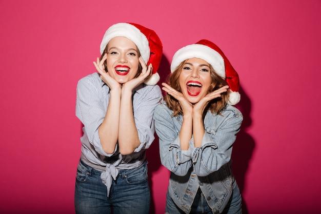 Animado, sorrindo, duas mulheres amigos usando chapéus de papai noel de natal