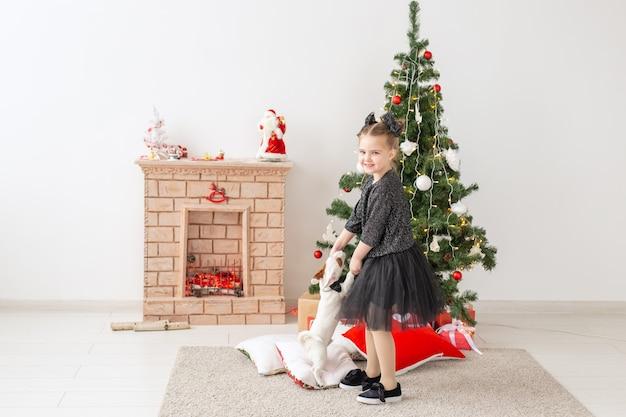 Animais de estimação, feriados e conceito de natal - menina criança brincando com o cachorrinho jack russell terrier perto da árvore de natal.