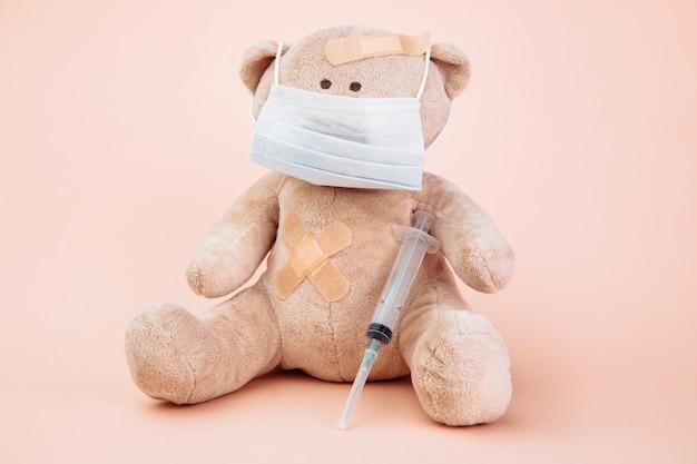Animal de urso empalhado em máscara com seringa isolada em rosa. conceito de pediatra