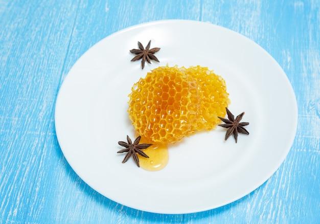 Anis e favos de mel redondos mentem em um prato em um azul.