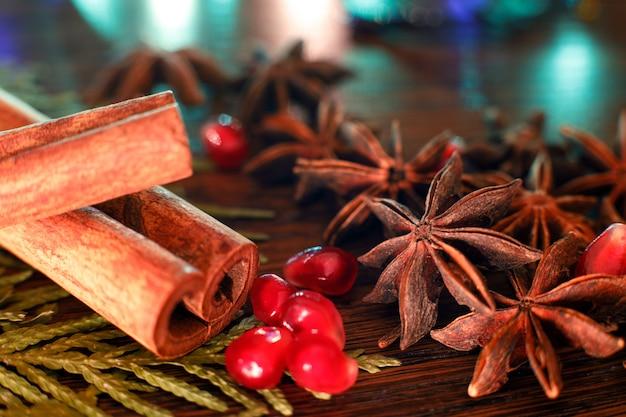 Anis, sementes de romã e paus de canela em uma mesa de madeira com luz de fundo colorida.