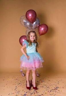 Aniversariante alegre em um vestido festivo fica no lugar da mãe em um fundo festivo