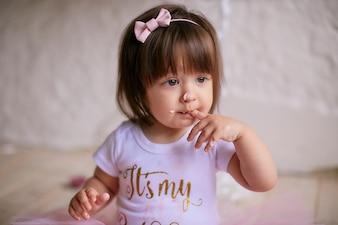 Aniversariante Bebê encantador no vestido rosa senta-se na cadeira