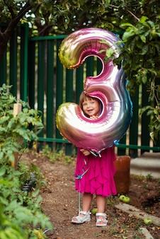 Aniversariante com balão em forma de três ao ar livre