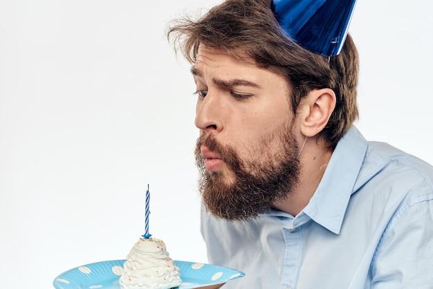 Aniversariante com um cupcake e uma vela em um chapéu de festa
