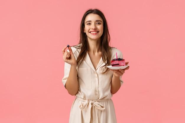 Aniversariante comer bolo delicioso, soprando velas e sorrindo alegremente, segurando mirtilo, festa comemorando o b-dia com os amigos, sorrindo em pé no vestido sobre parede rosa