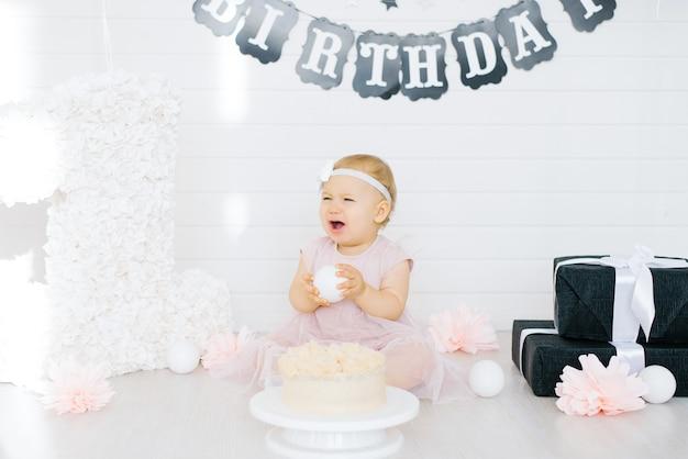 Aniversariante de 1 ano de idade sentada na área de fotos perto do bolo de aniversário