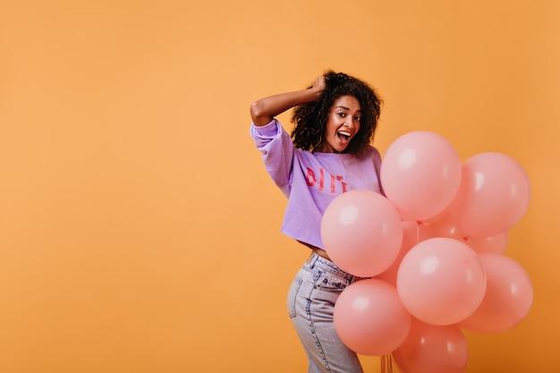 Aniversariante de cabelos escuros alegre dançando com um sorriso. bela jovem africana expressando espanto durante o ensaio fotográfico na festa.