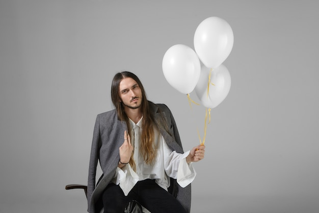 Aniversariante deprimido em roupas elegantes posando isolado com balões de hélio. foto horizontal de um jovem sério chateado com cabelo comprido solto e barba sentado na cadeira, segurando balões brancos