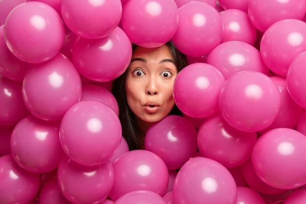 Aniversariante morena surpresa olhando com olhos esbugalhados mantendo a cabeça entre balões inflados