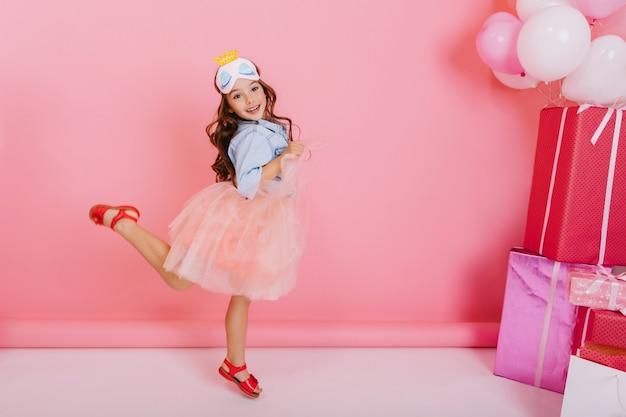 Aniversariante muito animada com longos cabelos castanhos, na saia de tule pulando, se divertindo isolado no fundo rosa. celebração brilhante de criança feliz incrível com caixas de presente e balões