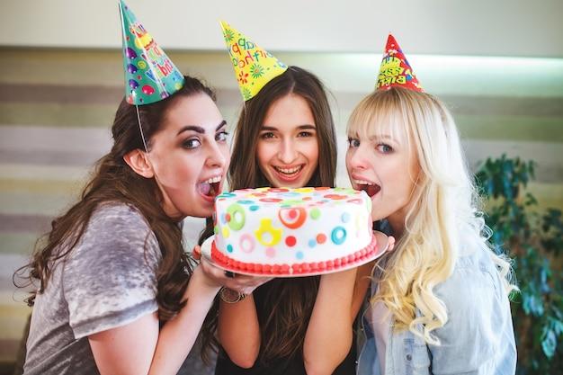 Aniversário. as meninas mordem o bolo em uma festa de aniversário.