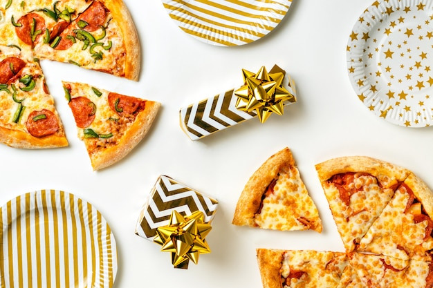 Aniversário com junk food. duas grandes pizzas saborosas com calabresa e queijo em um prato branco. presentes na mesa de férias. vista superior com espaço de cópia de texto. configuração plana