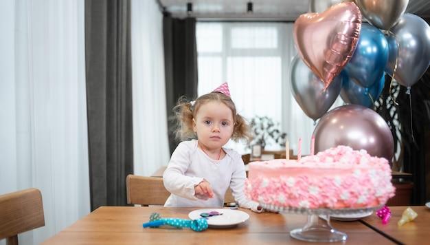 Aniversário da pequena princesa, bolo e balões de aniversário de videochamada online. a criança está sozinha