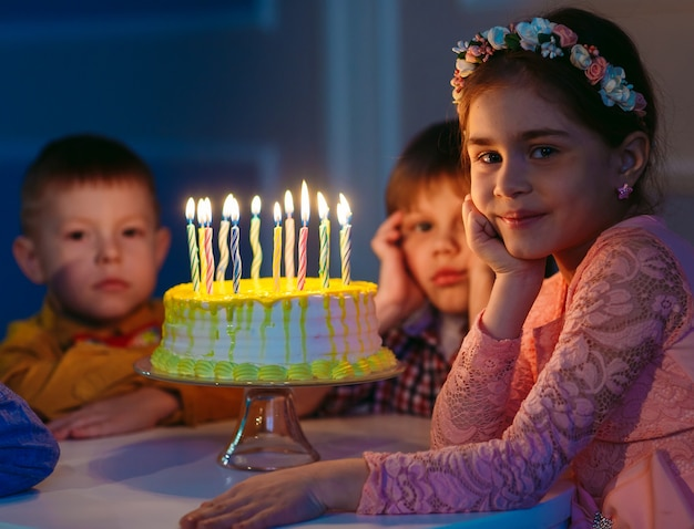 Aniversário das crianças. crianças perto de um bolo de aniversário com velas.