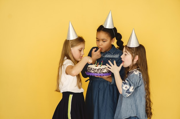 Aniversário de crianças pequenas isolado na parede amarela. crianças segurando bolo.