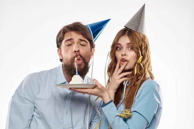 Aniversário de homem e mulher com um bolinho e uma vela em um chapéu de festa, fundo branco